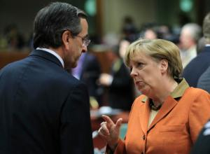 Greece's Prime Minister Antonis Samaras talks with Germany's Chancellor Angela Merkel during a European Union leaders summit at the European Council headquarters in Brussels