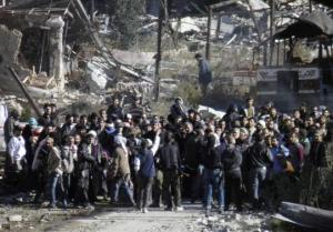 Civilians wait to be evacuated from a besieged area of Homs