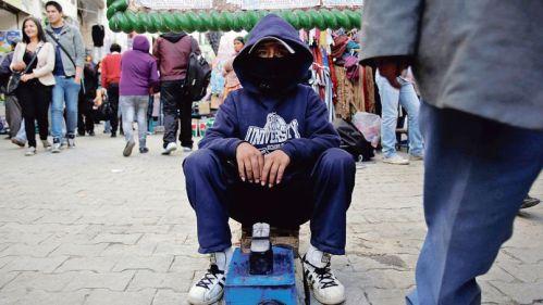 Boy working as a shoe shiner is seen in La Paz