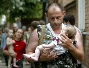 Russian police officer carries a released baby from the school seized by heavily armed masked men ...