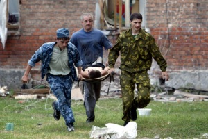 Volunteers carry an injured civilian to safety after soldiers stormed a school seized by heavily arm..