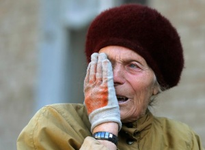 Maria Savchenko, 60, reacts as she sits in front of her home which was damaged by shelling a day before in the village of Pisky, near Donetsk in eastern Ukraine