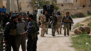 Rebel fighters gather along a street in the town of Babolin in Idlib countryside after retaking it from forces loyal to Syria's President Bashar al-Assad