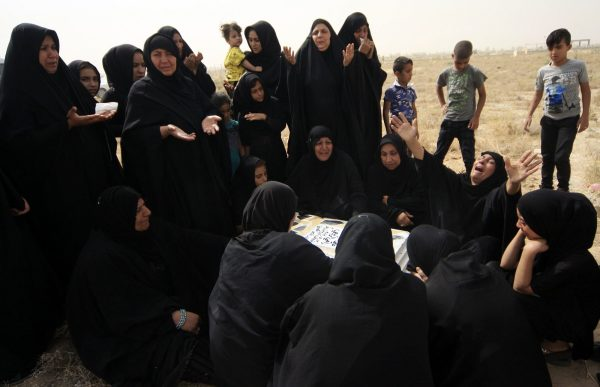 Women mourn over the tomb of their relative at a cemetery in Kerbala