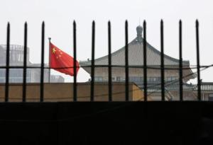 The national flag of China flutters behind a fence of the headquarters of the NDRC in Beijing
