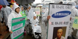 In this photo taken on March 25, 2010, South Korean activists wearing protective clothing, march after a rally near the Samsung semiconductor factory in Yongin, south of Seoul, South Korea, Thursday, March 25, 2010. Samsung Electronics said Thursday, April 15, 2010, workers at its semiconductor factories face no heightened cancer risk as the world's top maker of memory chips tried to quell health fears following employee illnesses and deaths. (AP Photo/ Lee Jin-man)