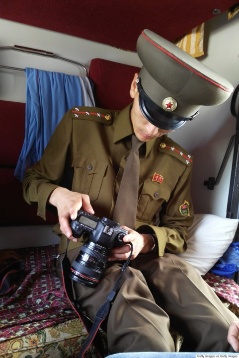 TUMANGANG, NORTH KOREA - AUGUST 19: A Customs officer checks a passenger's digital camera on the train No.100 from Moscow to Pyongyang at Tumangang railway station on August 19, 2015 in Tumangang, North Korea. North and South Korea today came to an agreement to ease tensions following an exchange of artillery fire at the demilitarized border last week. (Photo by Xiaolu Chu/Getty Images)