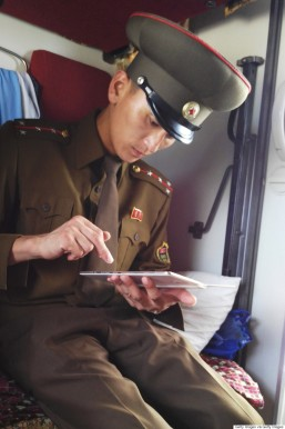 TUMANGANG, NORTH KOREA - AUGUST 19: A Customs officer checks a passenger's mobile device on the train No.100 from Moscow to Pyongyang at Tumangang railway station on August 19, 2015 in Tumangang, North Korea. North and South Korea today came to an agreement to ease tensions following an exchange of artillery fire at the demilitarized border last week. (Photo by Xiaolu Chu/Getty Images)