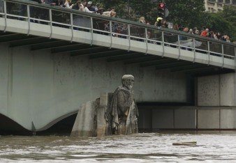 People stand on the Pont de l'Alma as they look at the Zouave statue covered by the rising waters from the Seine River after days of rainy weather in Paris, France, June 3, 2016 as the Zouave statue is considered an indicator of the level of the Seine, when his feet are under water, emergency flood precautions are taken. REUTERS/Pascal Rossignol