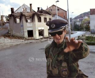 FILE PHOTO 28OCT92 - A soldier of the Bosnian Croat militia wearing a World War Two-vintage German cap waves away a photographer October 28, 1992 in front of gutted houses in the central Bosnian town of Prozor, shortly after the area was purged of Bosnian Moslem residents by Bosnian Croat forces allied to Zagreb, early into Bosnia's war. Croatian President Franjo Tudjman, whose death was announced December 11, was a communist general who turned to nationalism and led Croatia through war to independence from the crumbling Yugoslav federation in 1991. His hardline rhetoric and dubious human rights record did little to endear Tudjman to the West. But a clandestine attempt to divide neighbouring Bosnia with Yugoslav President Slobodan Milosevic during the 1992-95 war and to annex Croat territories remained his cardinal sin. CLH/