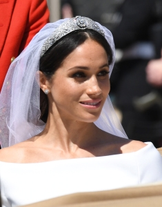 The Duke and Duchess of Sussex, Prince Harry and his new wife Meghan Markle smile and wave as they ride past the crowds on a horse drawn carriage in Windsor, UK.