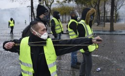 "A demonstrator uses a slingshot to throw projectiles at police during a protest of Yellow vests (Gilets jaunes) against rising oil prices and living costs, on the Champs Elysees avenue in Paris on December 1, 2018. - Thousands of anti-government protesters are expected today on the Champs-Elysees in Paris, a week after a violent demonstration on the famed avenue was marked by burning barricades and rampant vandalism that President Emmanuel Macron compared to ""war scenes"". (Photo by Lucas BARIOULET / AFP)"