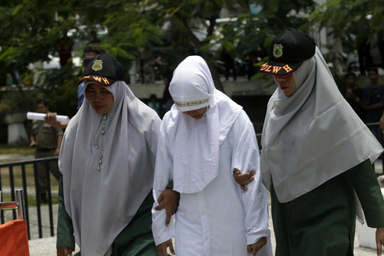 epa07852722 Sharia Police escort an Acehnese woman before she is caned in public for having sex outside of marraige in Banda Aceh, Aceh, Indonesia, 19 September 2019. Aceh is the only province in Indonesia that has implemented Sharia law and considers lesbian, gay, bisexual relationships and sex outside of marriage as Sharia law violations. EPA/HOTLI SIMANJUNTAK