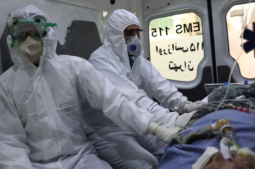0_Emergency-medical-staff-wearing-protective-suits-sit-in-an-ambulance-while-transferring-a-patient-w